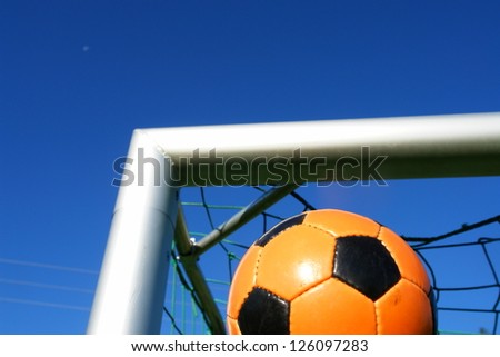 Goal. a soccer ball in a net. outdoors