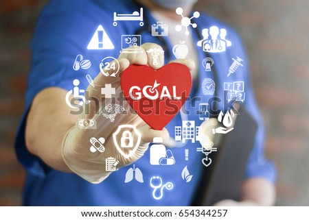 GOAL Health Care. Target in medicine treatment. Medical Success Strategy Plan Concept. Purpose achievement in hospital work. Doctor offers heart with goals icon on virtual screen. Healthy life style. ストックフォト ©