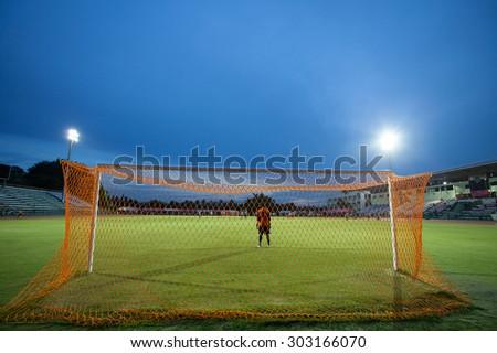 Goal keeper with stadium lights at night and stadium