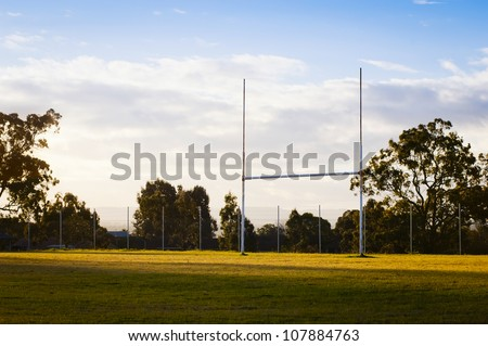Goal posts for football, rugby union or league on field at sunset