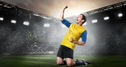 Goal scored. Excited soccer or football player is celebrating success on stadium. Happy team sports player kneel on field.