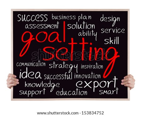 goal setting and other related words handwritten on blackboard with hands