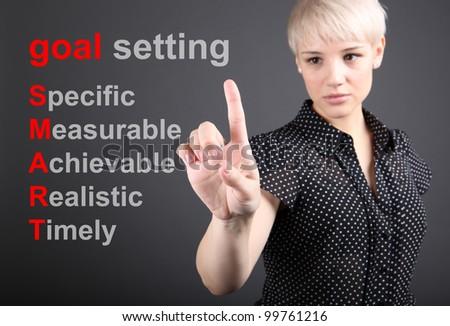 Goal setting concept - business woman touching screen
