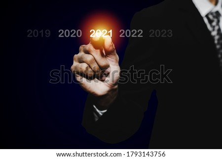 Goal target. businessman hand touching and pointing with pen on year 2021 with virtual screening on dark background, change from 2010 to 2021, strategy, business planning and happy new year concept Stockfoto ©