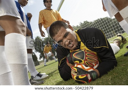 Goalkeeper on ground holding soccer ball, portrait