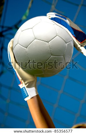 goalkeepers hands holding a soccer ball