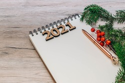 Goals and New year's resolution concept. New year 2021 goals list.  pen, notebook and christmas decorations isolated on a wooden background with copy space.