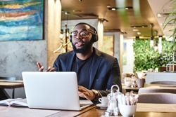 Goals are dreams with deadlines. Young businessman with headphones sitting in cafe in front of laptop and networking