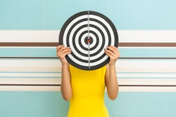 Goals concept with young woman holding target on blue background.
