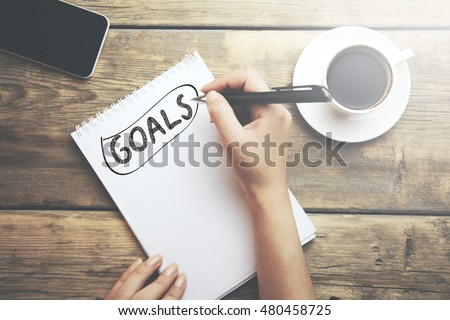 Goals memo written on a notebook with woman hand pen #480458725