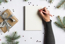 Goals plans dreams make to do list for new year christmas concept writing in notebook. Woman hand holding pen on notebook with fir branches gift on white background. New year winter holiday xmas