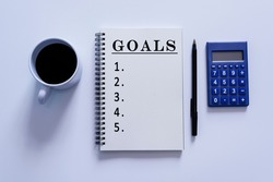 Goals text on notepad with pen, calculator and a cup of coffee on white background