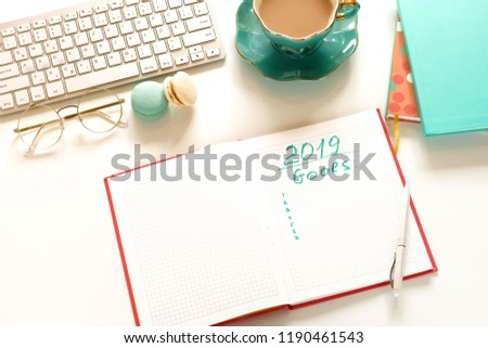 Goals 2019, To do list concept .top view, flat lay women's office desk. Female workspace with laptop, accessories, open notebook mock up, cup of cocoa on white background. Copy space.