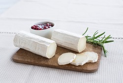 Goat cheese on a wooden board on a light background.