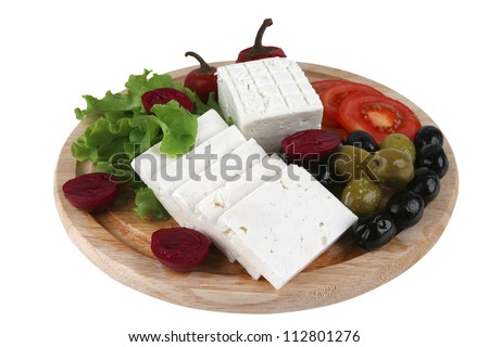goat cheese served with vegetables on wooden plate