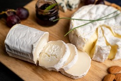 Goat cheese with other cheese and jam in the background on a cut board