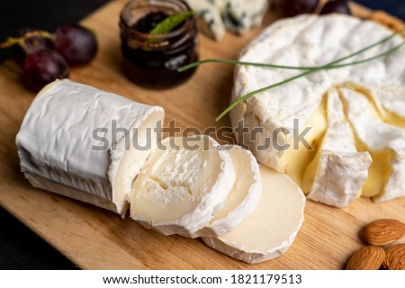 Goat cheese with other cheese and jam in the background on a cut board Foto stock ©