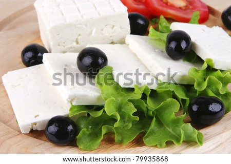 goat cheese with vegetables on wooden dish