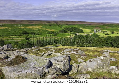 Goathland, Yorkshire, UK.  The North York Moors in summer showing rocks from the Jurassic, heather, and the undulating landscape near Goathland, Yorkshire, UK.