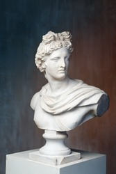 God Apollo bust sculpture. Ancient Greek god of Sun and Poetry Plaster copy of a marble statue on grange concrete wall background