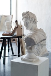 God Apollo bust sculpture. Ancient Greek god of Sun and Poetry Plaster copy of a marble statue on grange concrete wall background in studio. Copyspace for text