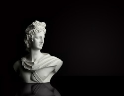 God Apollo bust sculpture. Ancient Greek god of Sun and Poetry statue isolated on black.
