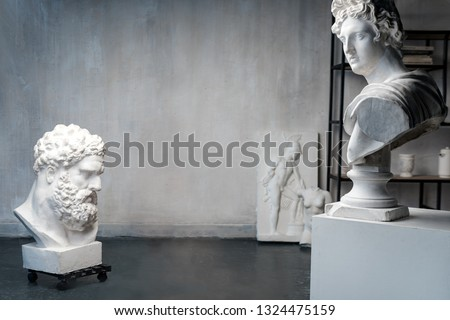 God Apollo bust sculpture and bust of the Farnese Hercules. Head sculpture, plaster copy of a marble statues of Greek gods and heroes on grange concrete wall background in studio. Copyspace for text.