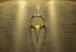 God Jesus Christ's blessing on the marriage relationship between husband and wife. Shiny golden engagement ring on open Holy Bible shadow forming heart. Faithful love, commitment, devotion, covenant.