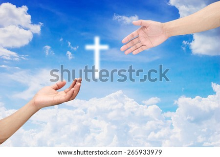 god\'s hands giving white cross for rescue human on blurred sky backgrounds.hands isolated on blurred backgrounds.