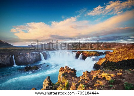 Godafoss waterfall at sunset. Fantastic landscape. Beautiful cumulus clouds. Iceland, Europe #705184444