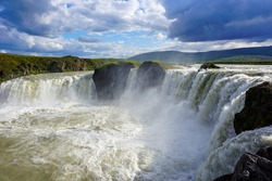 godafoss waterfall, beautiful clouds are in the sky, splashes of water rise into the sky, nature of Iceland