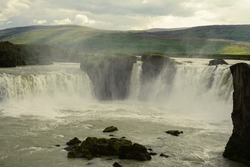 godafoss waterfall in summer cloudy weather, splashes of water rise up, there are beautiful clouds in the sky, nature of Iceland