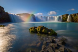 Godafoss Waterfalls, Iceland on a clear sunny day, with ice forming on the waters surface and the sun shining through the falls