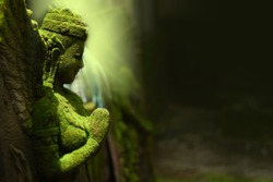 Goddess statue made of sandstone. According to Buddhist beliefs. Hindu and Brahman The moss is green because it is located outdoors. In the tropics Southeast Asia, Thailand, Myanmar, Cambodia,