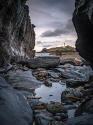 Godrevy Lighthouse, Cornwall, England against the darkening sky at dusk. The image is framed by barnacle covered brown rock outcrops.  A rock pool fills the foreground.