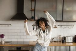 Going crazy. Funny positive young african female dancing at modern kitchen in good mood laughing having fun alone. Joyful millennial black female relaxing on weekend moving in dance by active music