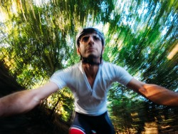 Going down in the forest; front view of a young male biker while riding fast on a single track in the wood. Intentional motion blur effect.