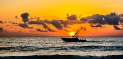 Going Fishing at Sunrise.  A boat equipped for recreational fishing heading out to fish in the sunrise from a beach in south florida