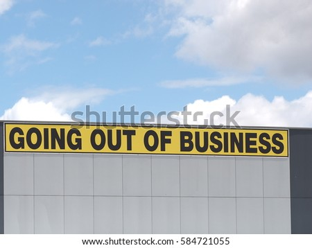 Going out of business writing in black on yellow letters on a white claded industrial building, Melbourne 2016