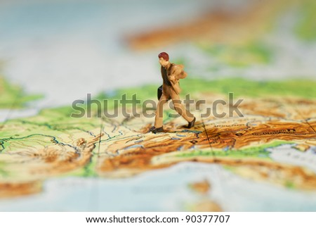 Going The Extra Mile In Business, macro of a miniature model businessman with briefcase striding across a map, concept with shallow DOF. - stock photo