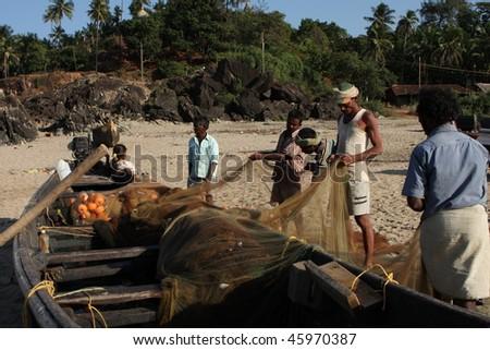 GOKARNA, INDIA - DECEMBER 14: Fishermen from Indian state Karnataka, prepare gear for fishing in the Indian ocean, December 14, 2008 in Gokarna, India. - stock photo