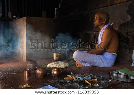 Gokarna, India - March 3, 2009: A hindu man praying and offering food and gifts to a recently deceased relative in Gokarna, an important pilgrimage site in South India