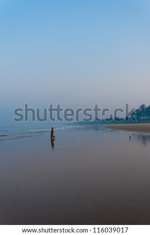 GOKARNA, INDIA - MARCH 2: A Hindu woman walks on the beach in the morning to pray for blessing in the ocean in Gokarna, a holy pilgrimage site, on March 2, 2009 in Gokarna, India