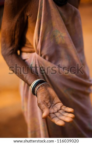 Gokarna, India - March 9, 2009: A poor old Indian senior woman extending her hand and open palm begging for money and change