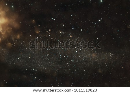 Gold and black glitter lights background. defocused - Shutterstock ID 1011519820