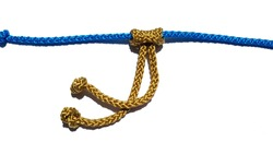 gold and blue prusik knot .rope knot isolated on a white background as a strong rock climbing line tied together as a symbol for trust and faith