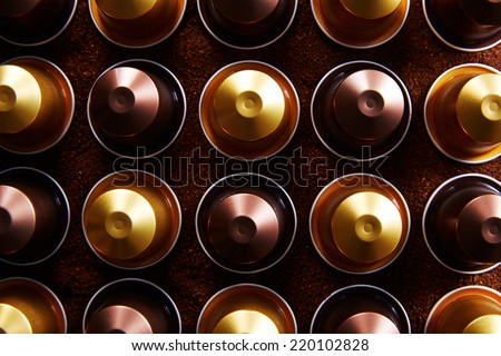Gold and brown coffee capsules on coffee background