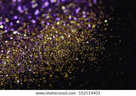Gold and purple glitter on black background with selective focus