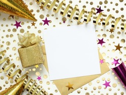 Gold and purple party background with streamers, confetti, hats, gift box and empty paper with envelope. Birthday, celebration, anniversary,  New Year, carnival concept. Top view, flat lay.