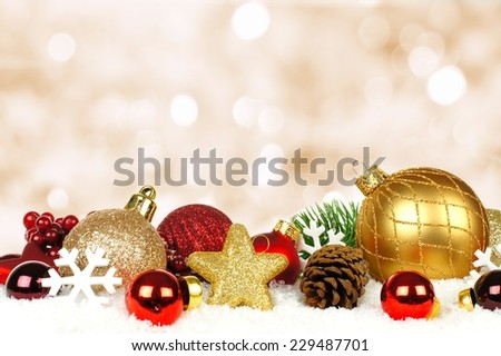 Gold and red Christmas ornament border in snow with twinkling gold light background